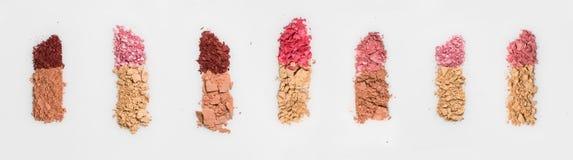 由被碰撞的面粉做的套七支唇膏和在白色背景脸红, 免版税图库摄影