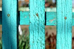 由被绘的绿色做的木农村篱芭的片段变老了在庭园花木背景的板条bokeh的 免版税图库摄影