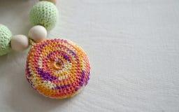 由被编织的小珠和玩具做的项链坐在吊索的婴孩的 被编织的小珠 吊索项链 免版税图库摄影