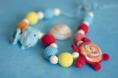 由被编织的小珠和玩具做的项链坐在吊索的婴孩的 被编织的小珠 吊索项链 免版税库存照片