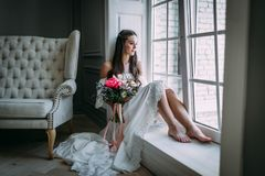 由视窗的妇女 看窗口的新娘,她等待新郎 免版税库存照片