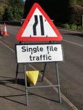 由说单一文件交通路的边的公路交通标志 免版税库存照片