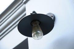 由路旁墙壁的一个开放电灯泡 库存照片
