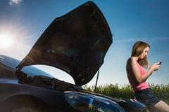 由路旁的俏丽,少妇在她的汽车以后身体垮下来了 库存照片