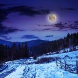 由路的篱芭向山的多雪的森林 免版税库存图片
