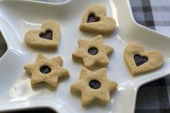 由酥皮糕点酥皮点心和曲奇饼做的圣诞节甜点,用巧克力充满橘子果酱和装饰的各种各样的形状 免版税库存照片