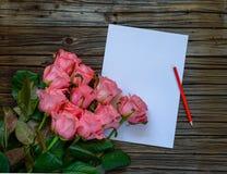 由铅笔和纸的十二朵桃红色玫瑰在木桌上 库存照片