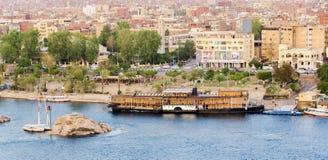 由阿斯旺市地平线的尼罗河与小船 免版税图库摄影