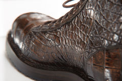 由鳄鱼皮革鞋带做的人的鞋子 库存照片