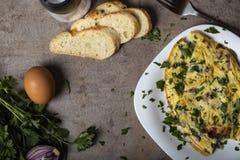 由鸡蛋、烟肉、乳酪和葱做的煎蛋卷在板材 库存照片