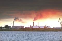 由从二个工厂烟囱出来的烟的大气污染 工业区在城市 库存图片