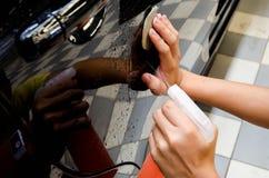 由黏土酒吧递擦亮,并且黏土润滑剂为取消汽车表面上的土 库存照片