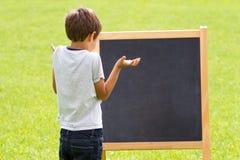 由黑板的想法的孩子户外 库存照片