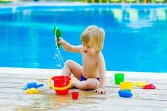 由水池的小孩与玩具桶集合 免版税库存图片