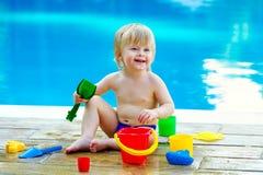 由水池的小孩与玩具桶集合 免版税图库摄影
