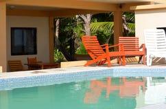 由水池的橙色椅子 免版税图库摄影