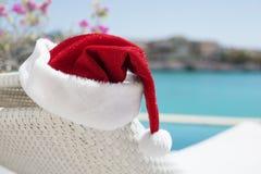 由水池的红色圣诞节帽子 库存照片