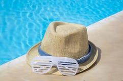 由水池的草帽和党太阳镜 免版税图库摄影