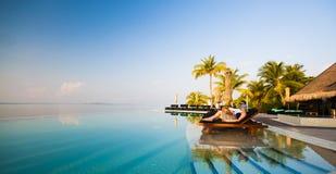 由水池结合放松在豪华热带旅馆里 免版税库存照片