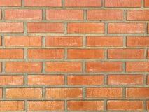 由水泥的水平的橙色砖墙举行 库存照片
