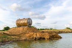 由水的被腐蚀的和生锈的储油桶反对好漂亮的东西或人 库存图片