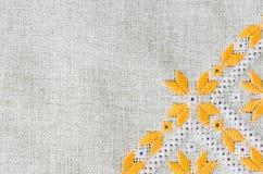 由黄色和白色棉花的刺绣设计在胡麻穿线 与刺绣的背景 免版税库存照片