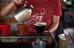 由Barista人咖啡店滴下咖啡我的黑杯 免版税库存图片