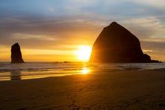 由Hastack岩石的日落在沿俄勒冈海岸的大炮海滩 免版税库存照片