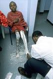 由Maasai男孩的腿的医生的药物治疗 库存图片