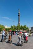 由segway的游客旅行在克里斯托弗・哥伦布附近,巴塞罗那,西班牙雕象  免版税库存图片