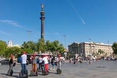 由segway的游客旅行在克里斯托弗・哥伦布附近,巴塞罗那,西班牙雕象  免版税库存照片