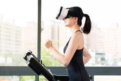 由VR耳机玻璃的秀丽亚裔妇女连续踏车 免版税库存图片