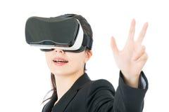 由VR耳机玻璃设备的亚洲女商人控制 图库摄影