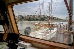 甲板船和Kastela市的看法比雷埃夫斯在一个雨天期间通过玻璃用水下降 库存照片