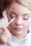 申请与刷子在女性眼睛的颜色眼影膏的化妆师 库存图片