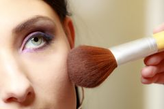 申请与刷子粉末胭脂的化妆师 免版税库存照片