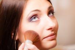 申请与刷子粉末胭脂的化妆师 免版税图库摄影
