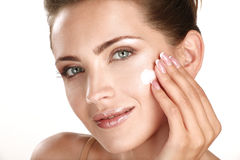 申请在她的面孔的美好的模型化妆奶油色treatmen 免版税库存图片