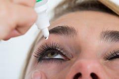 申请在白色背景的妇女眼药水 图库摄影