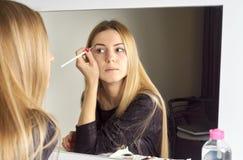 申请她的构成的年轻美丽的妇女的反射 免版税库存照片