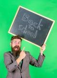 申请引起轰动的教育提议 人有胡子的老师拿着黑板回到在绿色的学校题字 图库摄影