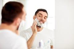 申请愉快的人刮泡沫在卫生间镜子 免版税库存图片
