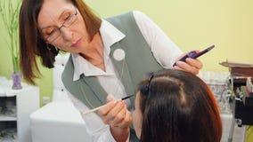 申请构成的化妆师于有化妆用品刷子的妇女在秀丽演播室 做构成面孔的Visagiste对秀丽 股票录像