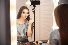 申请构成的可爱的少妇在镜子附近 免版税库存图片