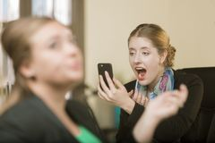 申请构成的妇女使用她的电话作为镜子 库存图片