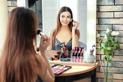 申请构成的年轻美丽的妇女在镜子附近 免版税库存图片