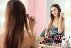 申请构成的年轻美丽的妇女在镜子附近 免版税库存照片