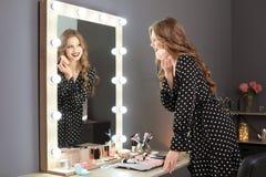 申请构成的美丽的妇女在镜子附近在化装室 免版税图库摄影