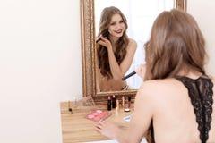 申请构成的美丽的妇女在镜子附近在化装室 免版税库存照片