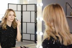 申请构成的美丽的妇女在镜子附近在化装室 库存图片